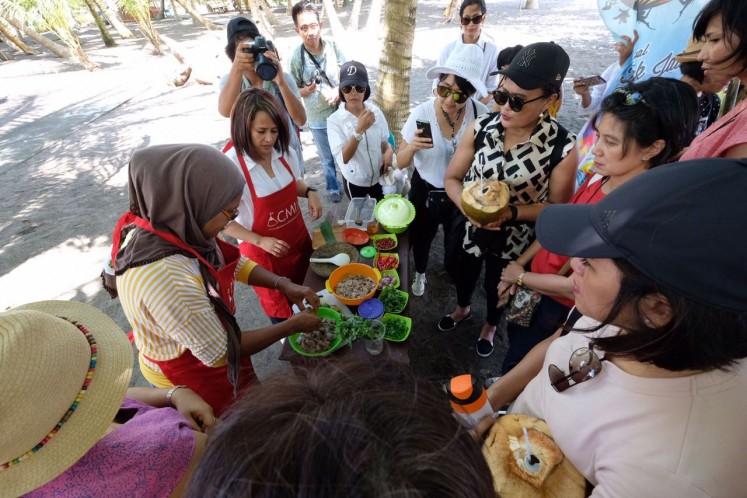 Tour participants enjoy a hands-on cooking demo at Lako Akelamo village, a coastal area in Jailolo, West Halmahera, North Maluku.