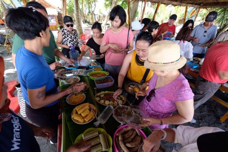 Tour participants sample traditional food at Lako Akelamo village, a coastal area in Jailolo, West Halmahera, North Maluku.