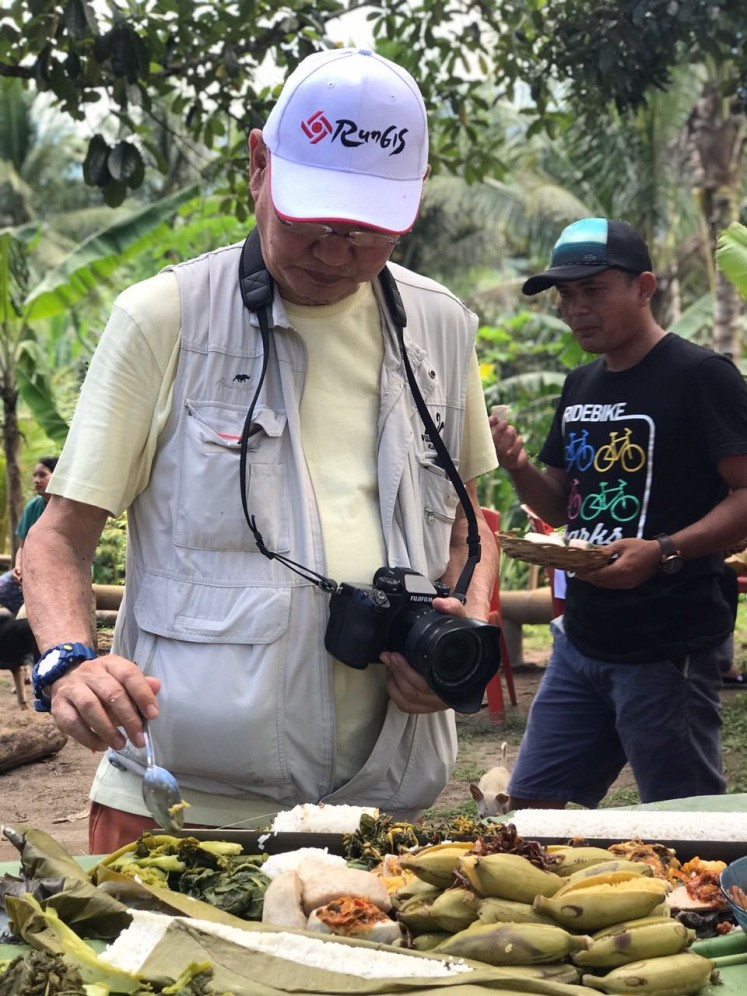 Culinary expert William Wongso samples food at Ngaon village, a farmland area in Jailolo, West Halmahera, North Maluku.