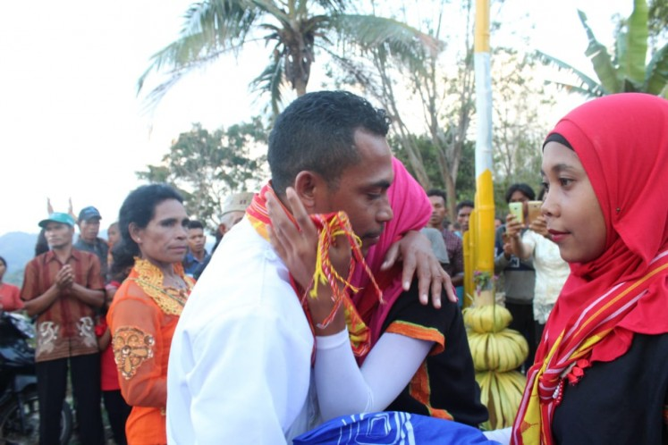 Rikardus receives an embrace to welcome him to the village | Markus Makur / Jakarta Post