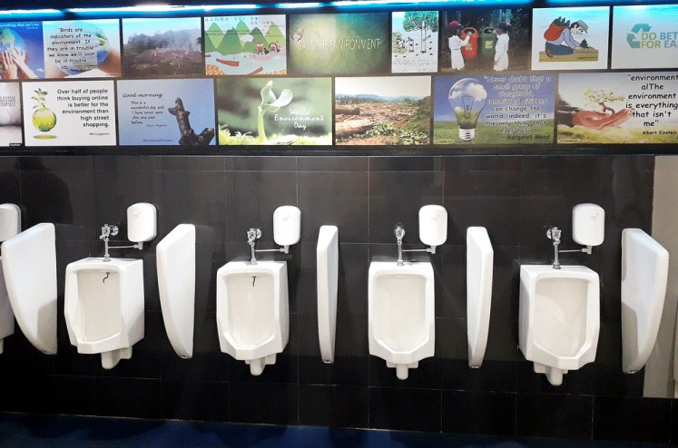 Save the forest: Posters and photos about saving the environment grace the walls of the public toilets at Sultan Syarif Kasim Airport in Pekanbaru, Riau.