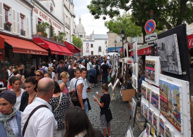 This file photo shows tourists look at the work of painters in Place du Tertre in the Montmartre district of Paris on August 16, 2015.