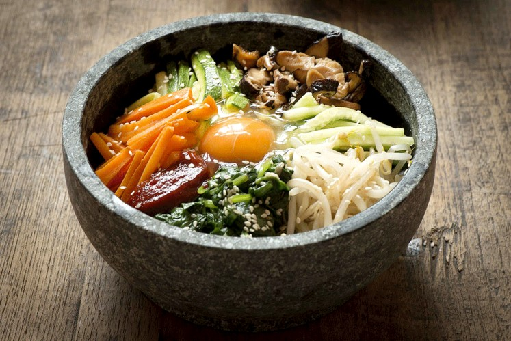 "Hot and spicy: Korean dish bibimbap, which literally means ""mixed rice"", is served as a bowl of warm white rice topped with sautéed vegetables, gochujang (Korean chili pepper paste) and soy sauce with raw or fried egg and slices of meat."