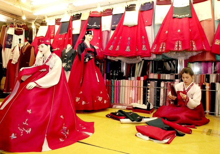 Korean style: A South Korean shop tailor checks fabric at the hanbok (traditional dress) market in Gwangju city, South Korea.