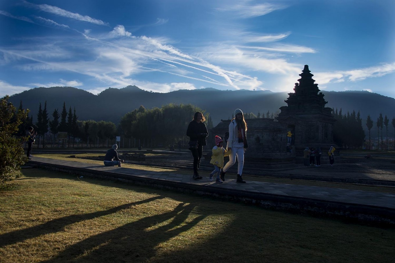 Visitors stick close together as they stroll through the Arjuna temple complex in the morning. JP/Tarko Sudiarno