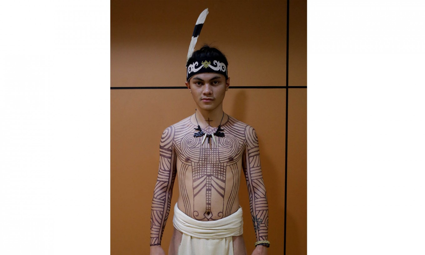 A male dancer wearing a Dayak traditional costume shows off his tattoos by artist Aman Durga Sipatiti at the Teater Jakarta. JP/Wienda Parwitasari