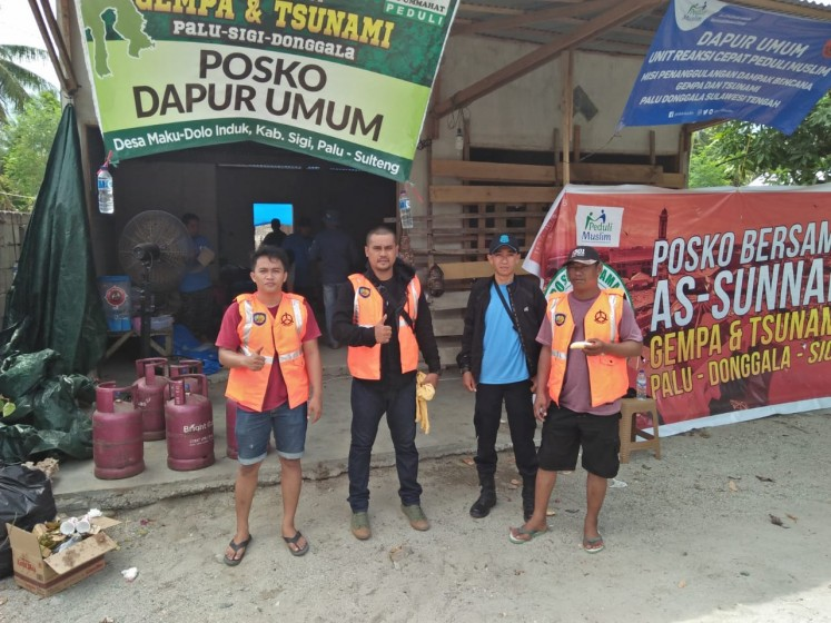 Inmates from Palu detention center in Central Sulawesi gather in front of a public kitchen in Palu, Central Sulawesi, on Oct. 11, while helping survivors.