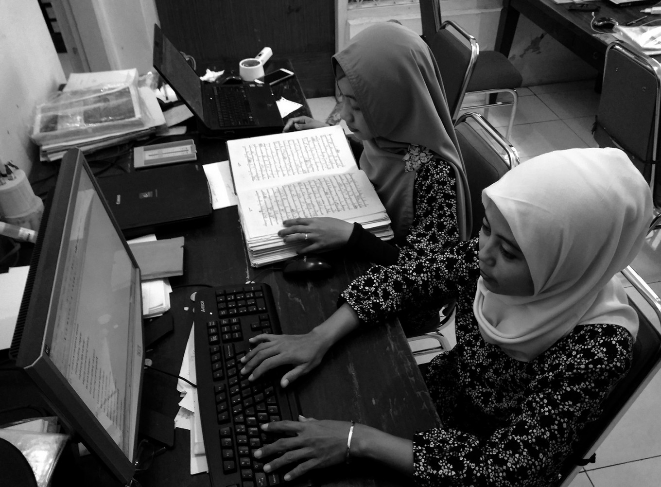 The rewriting process is done in pairs. One staff member reads while another types. JP/Ganug Nugroho Adi