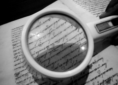 A magnifying glass is used to read the Javanese characters in a manuscript. JP/Ganug Nugroho Adi