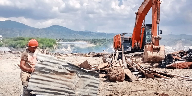 Workers use a backhoe to clear away debris on Wednesday at a destroyed warehouse complex in Mamboro, Palu city, Central Sulawesi, that was hit by last month's tsunami.