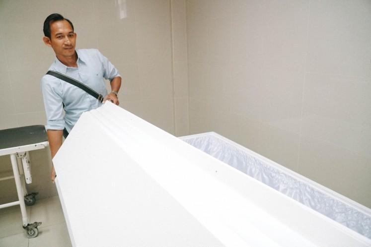 Yayasan Anugrah Kasih owner Benedictus Budiman shows the inside of a casket.
