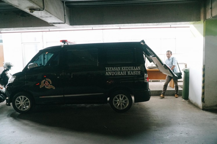 Benedictus Budiman checks Yayasan Anugrah Kasih's hearse in Rumah Duka Harapan Kita, West Jakarta.