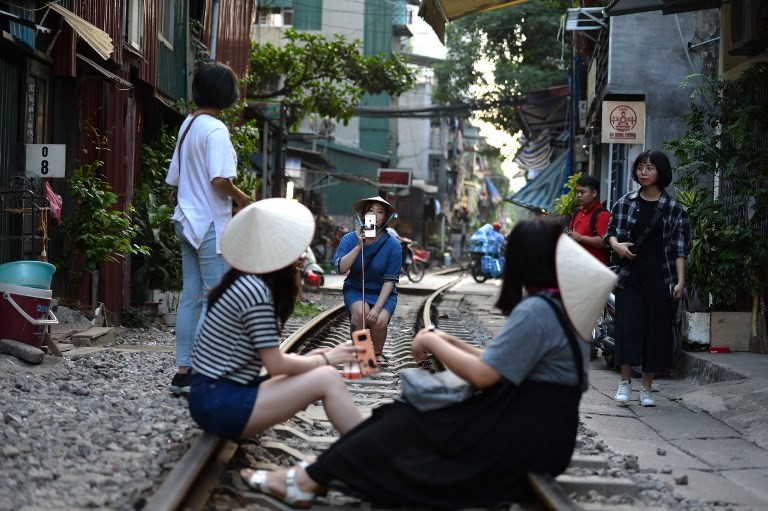 Tourists pose for a photo while sitting on a railway track passing through an old residential district in central Hanoi on Oct. 21, 2018. Image: AFP/Nhac Nguyen