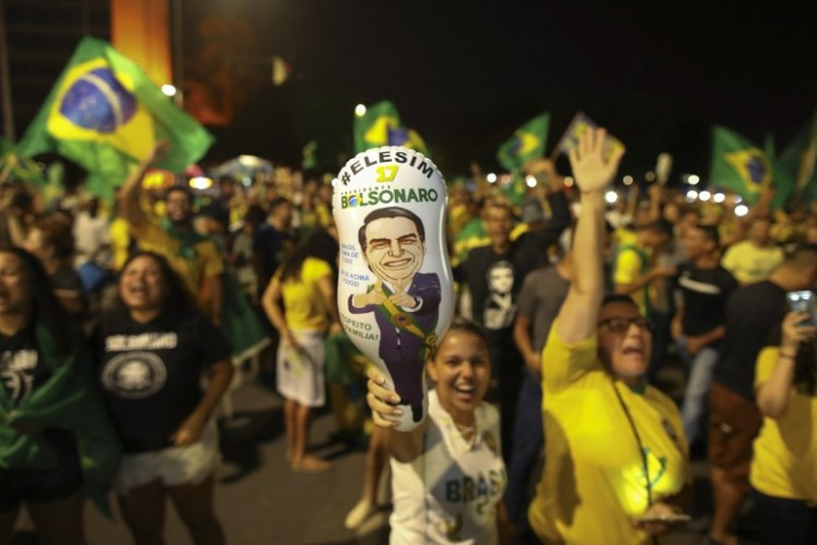 Supporters of far-right presidential candidate Jair Bolsonaro, celebrate in front of the National Congress in Brasilia, after the former army captain won Brazil's presidential election, on Oct. 28. Far-right former army captain Jair Bolsonaro was elected president of Brazil on Sunday, beating leftist opponent Fernando Haddad in a runoff election after a bitter and polarized campaign. Official results gave the controversial president-elect 55.18 percent of the vote with more than 99.7 percent of the ballots counted.