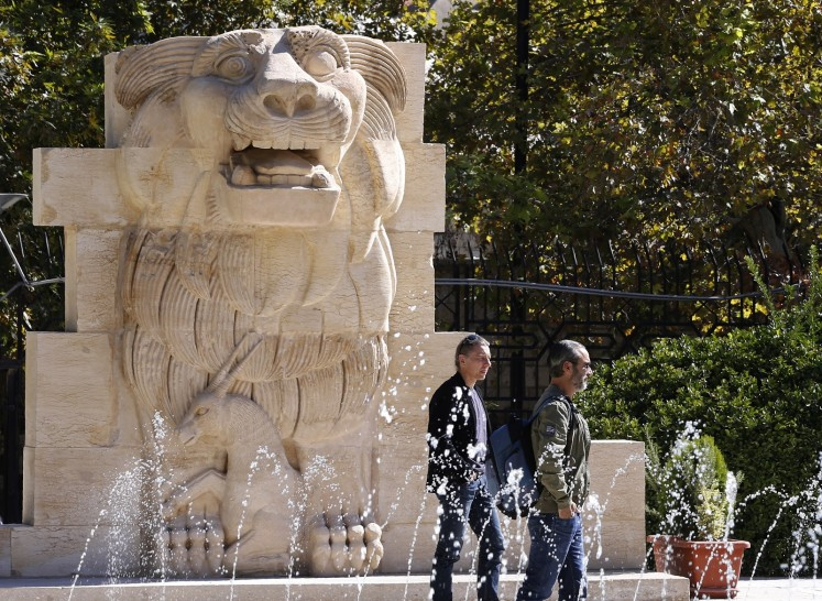 Visitors walk in front of the Lion of al-Lat, an ancient statue from the temple of the same name in Palmyra, during their visit to the national antiquities museum in the Syrian capital Damascus on October 28, 2018. Syria reopened a wing of the capital's famed antiquities museum today after six years of closure to protect its exhibits from the civil war