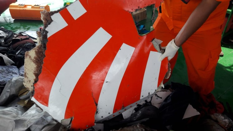 An SAR personnel shows a section of plane debris recovered near the location where Lion Air flight JT610 crashed into the sea on Monday morning off Karawang, West Java.