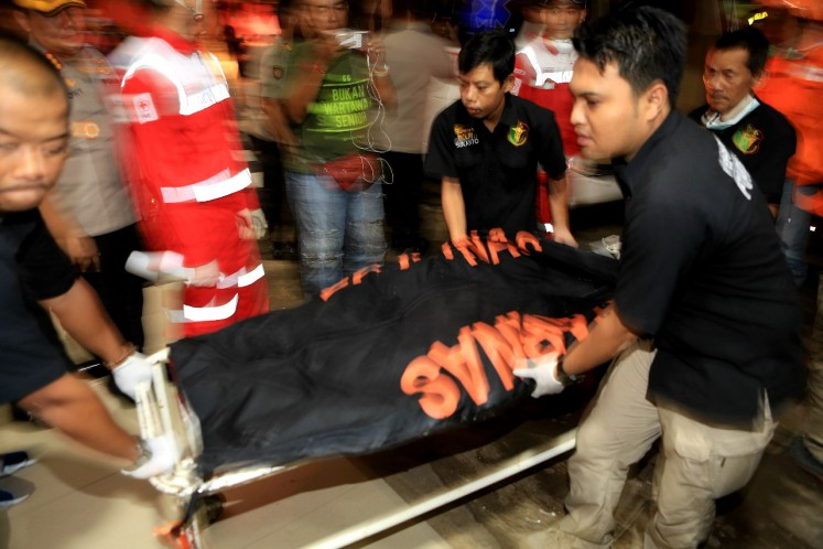 A forensics team carries bodies of the victims of Lion Air flight JT610 to Sukanto National Police Hospital, East Jakarta, on Monday.