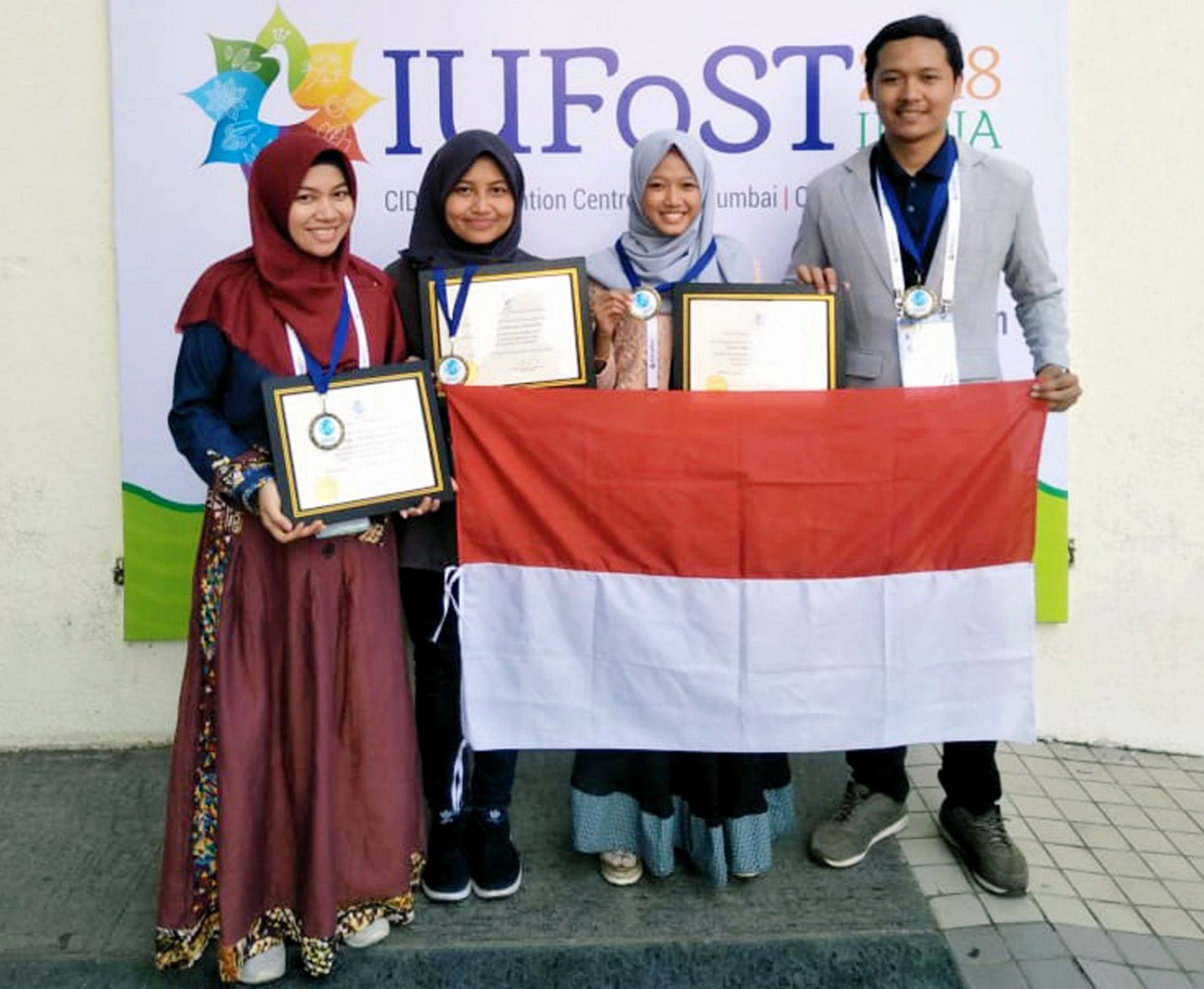 Alfisah Nur Annisa (kiri), Widya Nur Habiba (kiri kedua), Annisa Aurora Kartika (kanan ke dua) dan Joko Tri Rubiyanto (kanan) berpose dengan penghargaan yang mereka menangkan di International Union of Food Science and Technology (IUFoST) 2018 Pengembangan Produk Kompetisi di Mumbai, India, pada 27 Oktober (Sumber: Fakultas Teknologi Pertanian, Universitas Brawijaya)