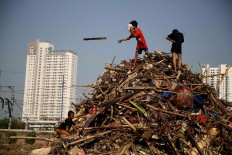 Children play on a pile of garbage consisting mainly of tree trunks, logs and bamboo in Tanah Abang, Central Jakarta, on Thursday, October 25, 2018. The garbage was collected from the West Flood Canal. JP/PJ Leo