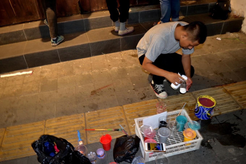 A mural artist mixes paints.