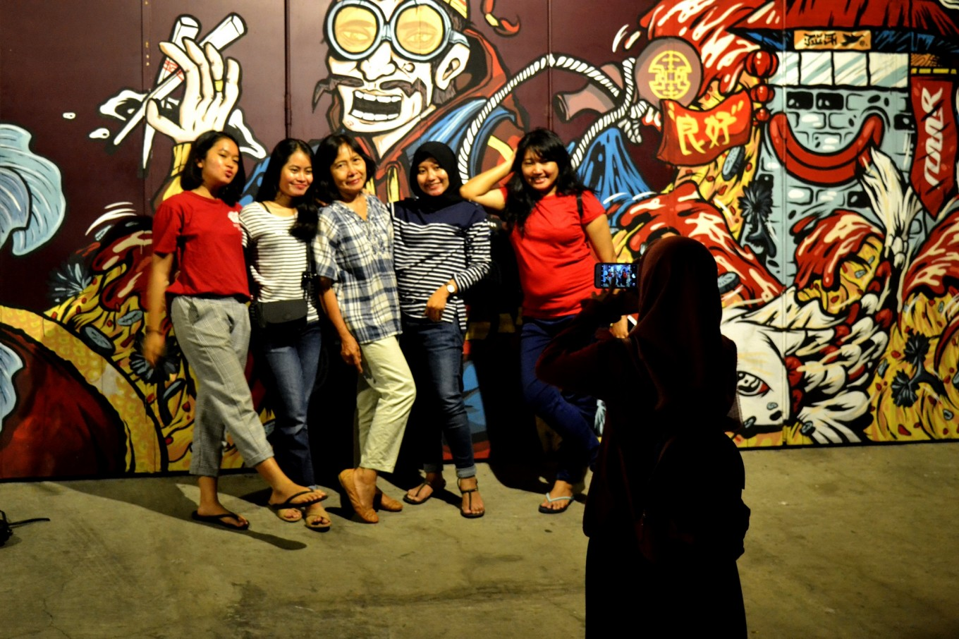Residents take a selfie in front of a mural.