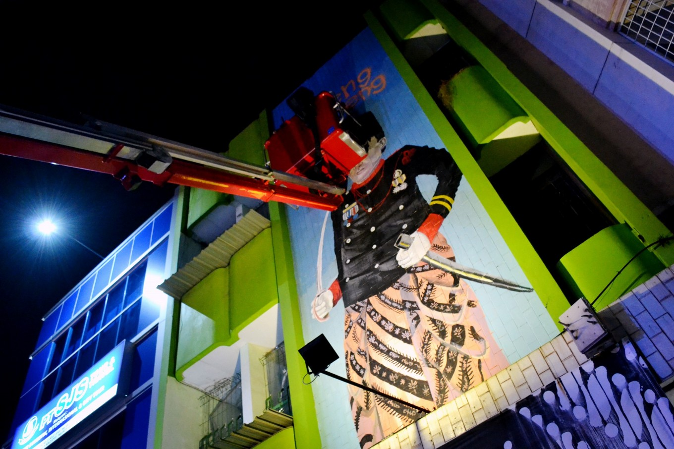 An artist paints a mural with the help of the fire brigade's equipment.