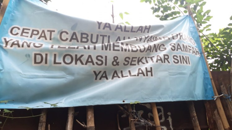 "A banner, found on the side of Jl. Aria Putra in Jombang, Ciputat, in South Tangerang, says, ""God, please take the lives of anyone who litters here!"""