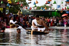 A man and a woman ride on rafts during the Sri Mulyono and Sri Mulyani performance, depicting the harmony of the water spring in Pluneng village. JP/Magnus Hendratmo