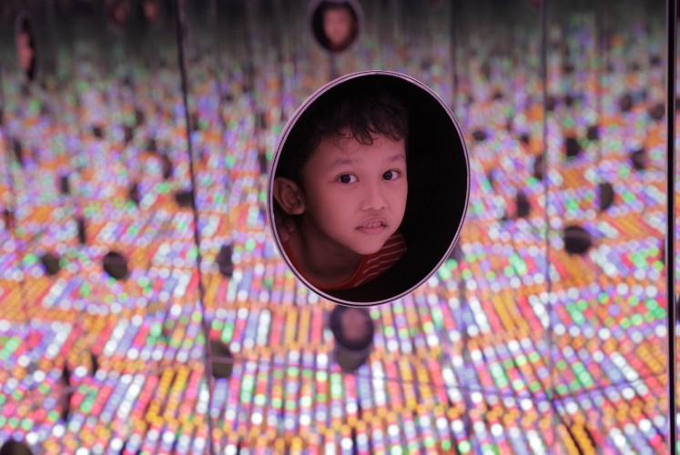 A child visitor peeps through the hole of 'I Want to Love on a Festival Night' ( 2015 ), an interactive installation at Yayoi Kusama's exhibition Life is the Heart of a Rainbow, which was held at Museum Macan  from May 12 to Sept. 9.