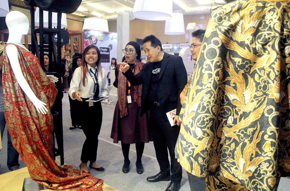 Creative Economy Agency (Bekraf) head Triawan Munaf (third left), accompanied by the deputy head for institutional relations' Endah Wahyu Sulistianti (second left), inspects the Creative Village booth at the World Conference on Creative Economy (WCCE) in Nusa Dua, Bali, on Tuesday. Image: The Jakarta Post/Zul Trio Anggono