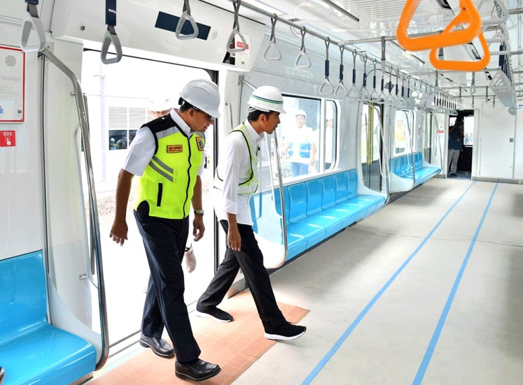 "President Joko ""Jokowi"" Widodo (right) and Jakarta Governor Anies Baswedan enter an MRT train at Bundaran HI Station on Tuesday for a test ride to Lebak Bulus Station. The first phase of MRT construction is reportedly 97 percent complete and the service is expected to begin operating in March 2019."