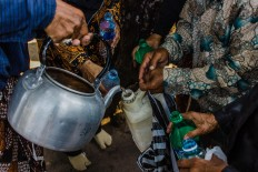 A courtier uses a kettle to distribute sacred water among the public. JP/Anggertimur Lanang Tinarbuko