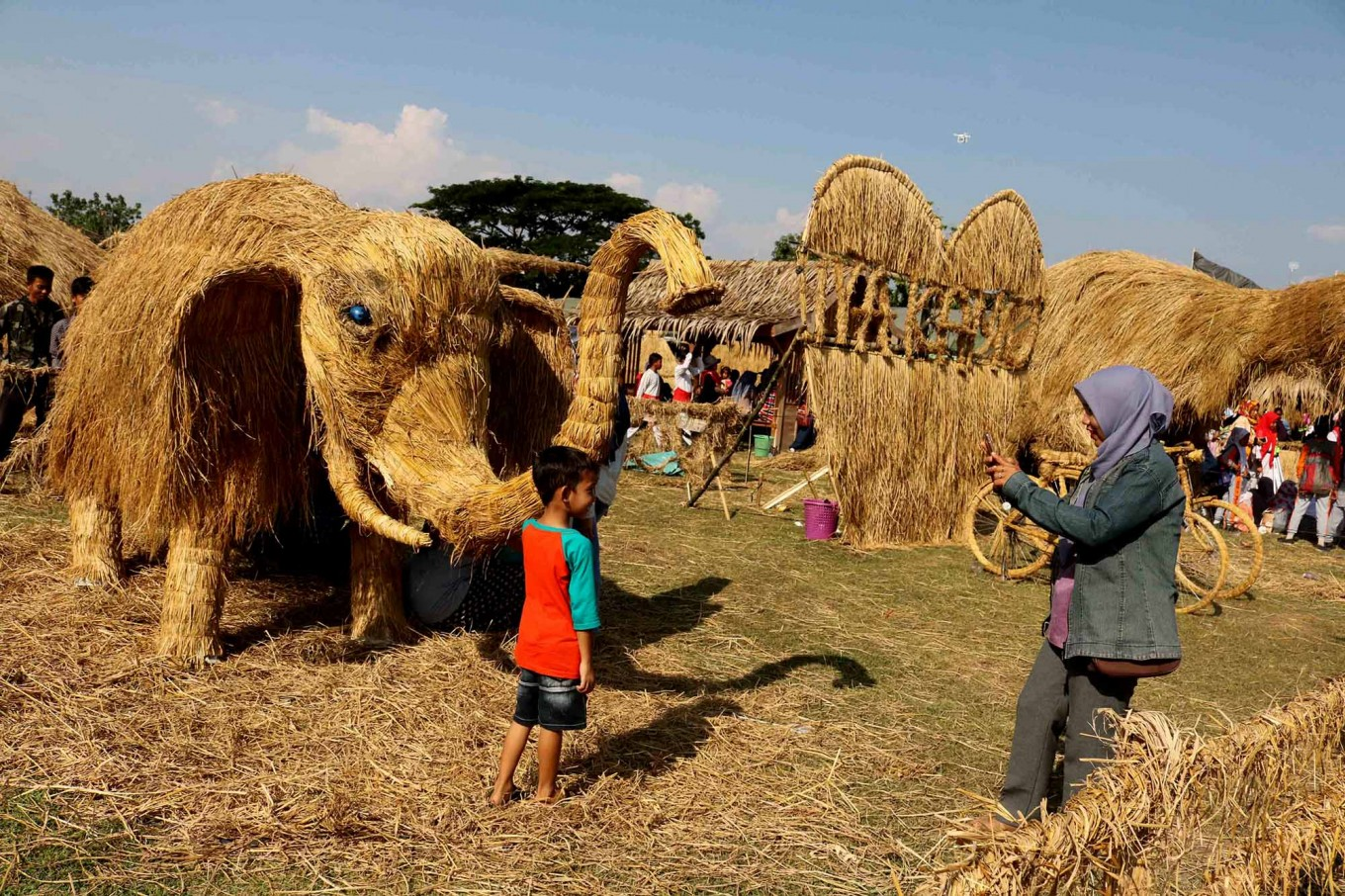 Prehistoric pal: A boy poses beside a Stegodon sculpture at the Straw  Festival, which celebrates discoveries from the prehistoric era in Banjarejo village, Grobogan, Central Java. JP/Maksum Nur Fauzan