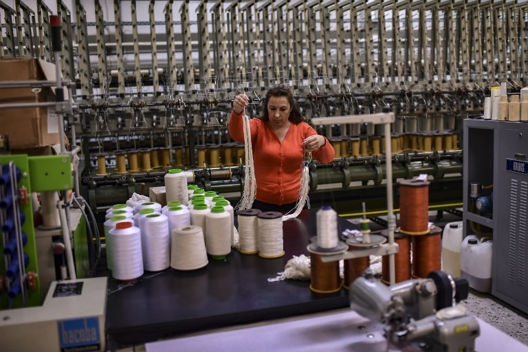 A woman works at a silk fabric factory in the Greek northern town of Soufli on October 10, 2018.