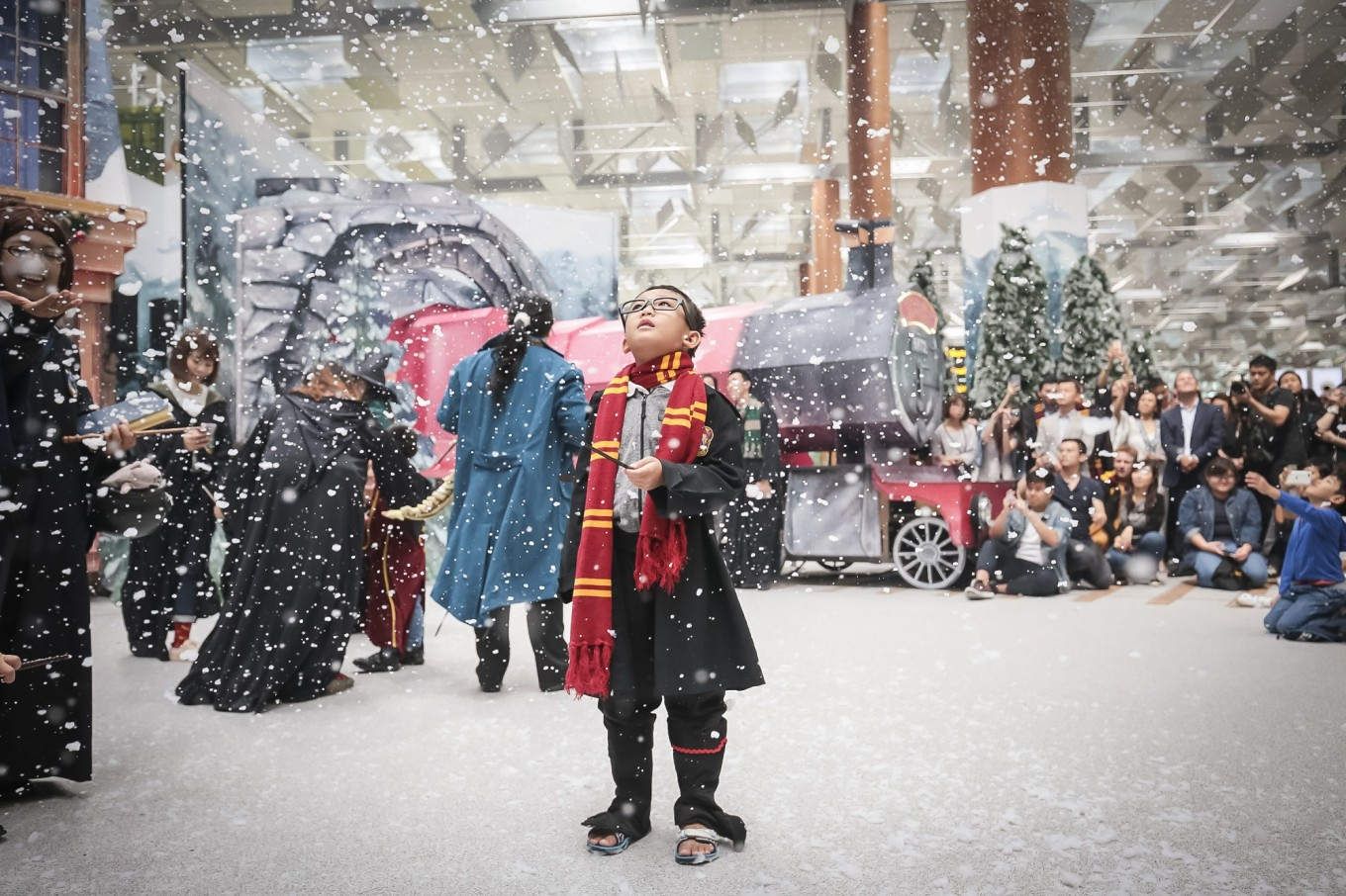 A young fan is enthralled by the snow at a wintry Hogsmeade Village-inspired setup at Changi Airport's Terminal 3 Departure Hall. Image: Changi Airport/File