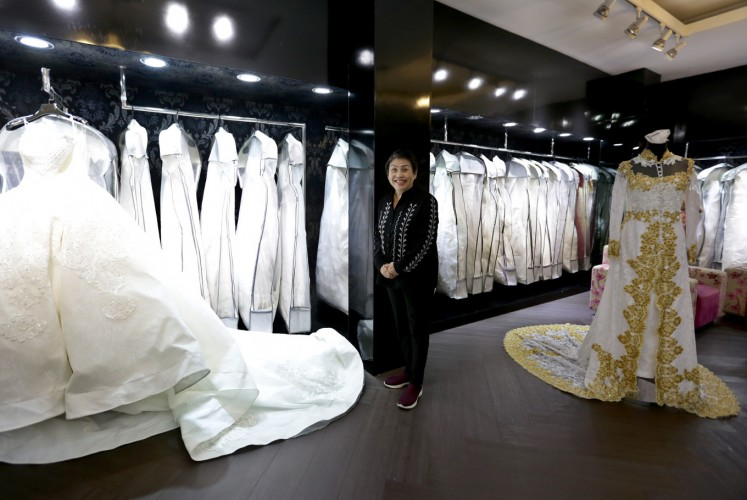 Eva, the owner of Eva Bun, stands amid her dresses at the Eva Bun Wedding Gallery in Central Jakarta on Friday.
