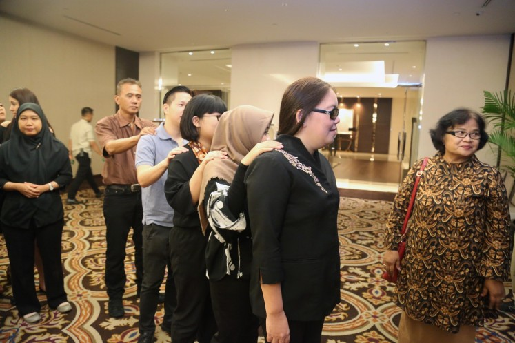 A visually impaired server from Yayasan Mitra Netra guides four journalists into Fairmont Jakarta's ballroom during the Dining in the Dark media event on Tuesday.