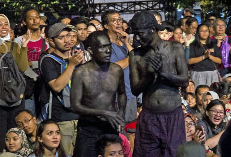 Paint it black: Two men painted black stand near the VVIP section of the 2018 Ngayogjazz Jazz Festival.