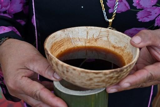 Foto ini diambil pada 28 November 2018 menunjukkan seorang wanita Indonesia memegang secangkir kopi Kawa Daun disajikan dalam tempurung kelapa selama festival seni dan budaya Minangkabau di Batusangkar, Sumatera Barat. Daerah ini adalah rumah bagi pengambilan yang aneh pada minuman yang mengekstrak rasa dari daun tanaman daripada kacangnya. Ini adalah minuman kuno yang berasal dari masa kolonial ketika sedikit penduduk setempat yang mampu membeli kopi yang diekstrak | Foto: Adek Berry / AFP