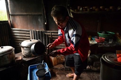 Foto ini diambil pada 29 November 2018 menunjukkan seorang pria membuat kopi Kawa Daun di sebuah kafe tradisional di Tabek, Sumatra Barat | Foto: Adek Berry / AFP