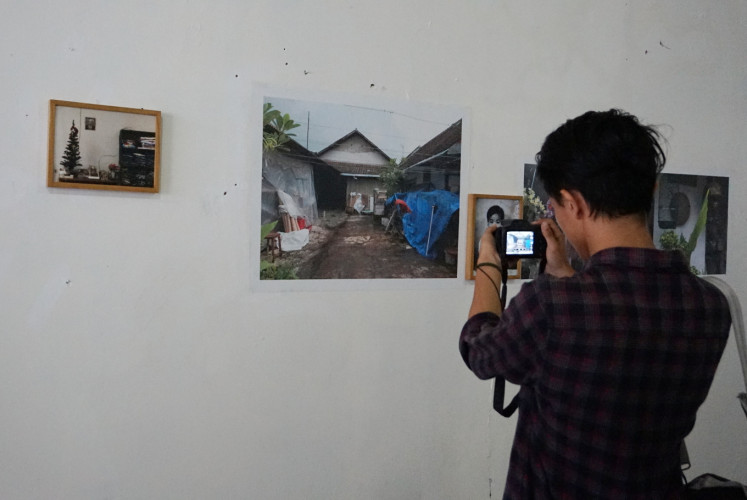 A photographer takes a photo at Ng Swan Ti's 'Rumah Masa Kecil' (Childhood House) exhibition at the launch of the #AkuSiapBersikap campaign on Nov. 27 at Budi Luhur University in Tangerang, Banten.
