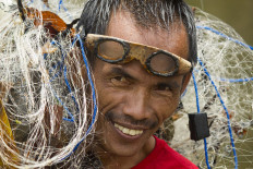 Satisfaction: A villager smiles after catching some fish with his nets. JP/Tarko Sudiarno