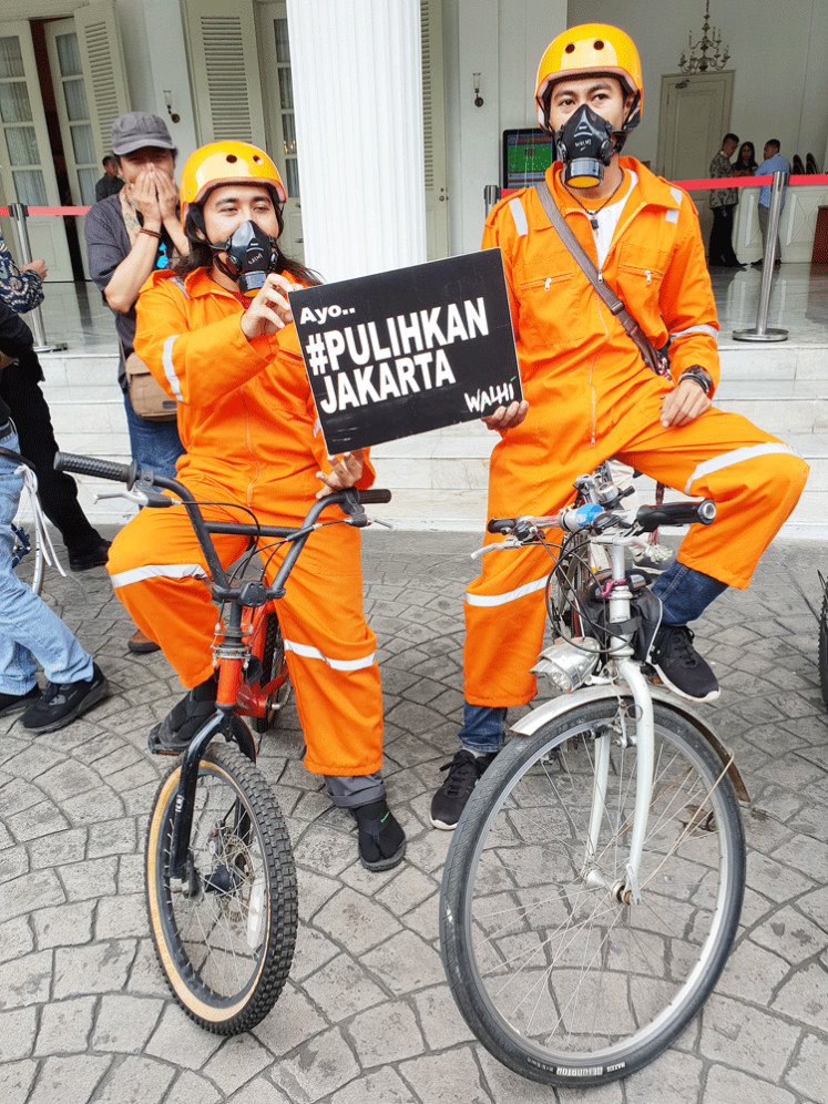Let's clean the air: Cyclists wearing safety gear and respiratory masks lead the symbolic handover of a civil lawsuit notification from a social movement called Gerakan Ibu Kota (Capital City Movement) to the Jakarta administration at City Hall, Central Jakarta, on Wednesday.