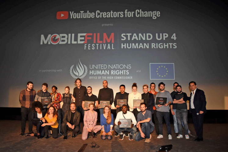 Creators for change: Mobile Film Festival founder Bruno Smadja (right, standing) strikes a pose with the winners and the judges at the festival's award ceremony on Tuesday in Paris, France.
