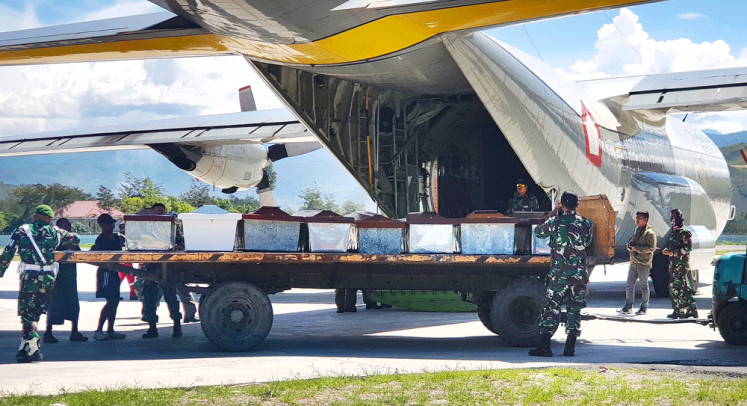 Time of loss: Indonesian Military officers load coffins into a carrier aircraft in Wamena, Papua, on Thursday. Indonesian security forces have retrieved the bodies of 16 people in the aftermath of a massacre of construction workers by separatist rebels in restive Papua province, the military said on Thursday.