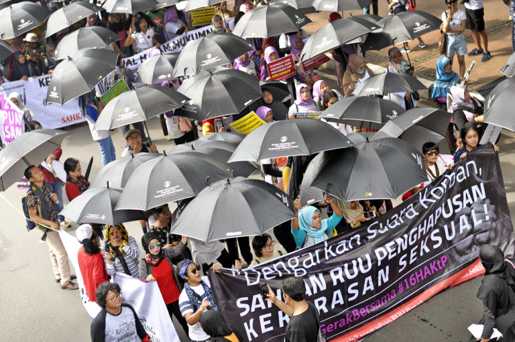 Standing up against sexual violence: Carrying black umbrellas, activists march on Jl. MH Thamrin, Central Jakarta, on Sunday toward Aspiration Park near the Presidential Palace. The activists held a mass rally as part of this year's global 16 Days of Activism Against Gender-based Violence campaign, during which they called on the government to immediately pass the sexual violence eradication bill  into a law.