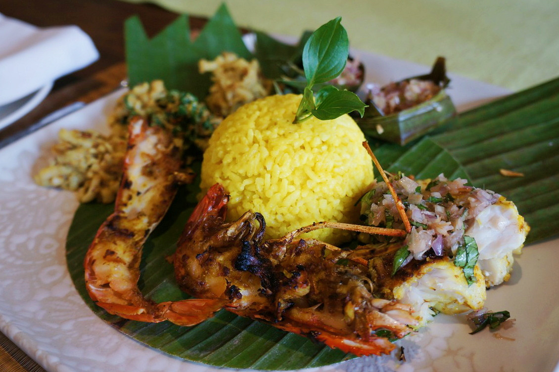 Grilled fish, prawns, squid and long beans 'lawar' salad with yellow rice and three types of 'sambal' at the Jala cooking academy, Four Seasons Bali at Jimbaran bay.