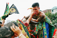 A tatung (a man possessed by a spirit) smears blood on someone's forehead during the parade. JP/Donny Fernando