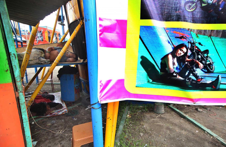 Sweet dreams: Men sleep beside a poster af a local stunt woman. JP/Boy T Harjanto