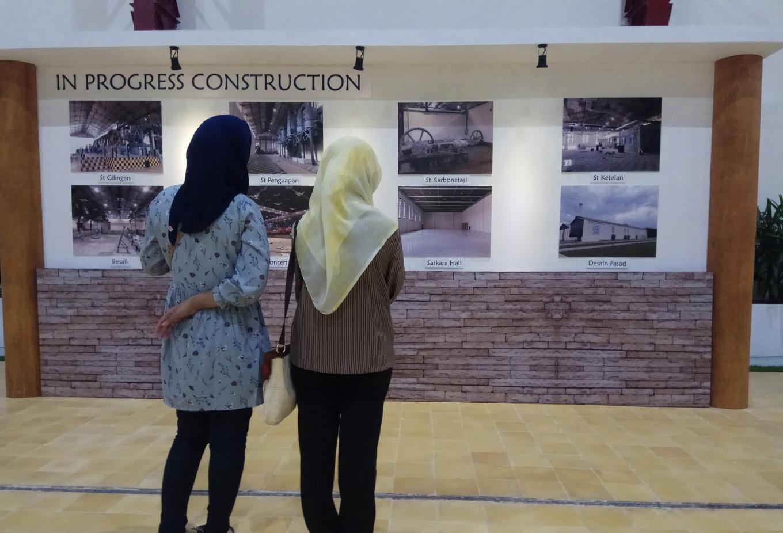 Visitors examine photos of De Tjolomadoe's development.